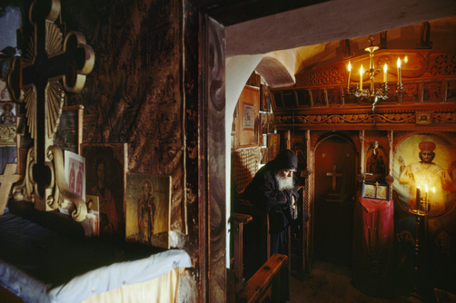 An Orthodox priest says his prayers in his home filled with icons.