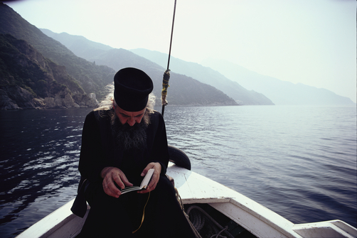 A monk reads scriptures on a rowboat in the Aegean Sea.
