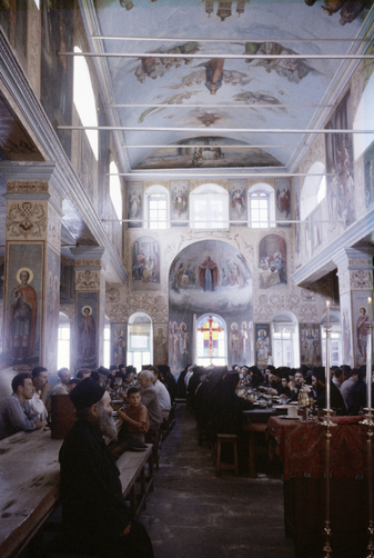 Monks and pilgrims feast on a saint's day in an ornate refectory.