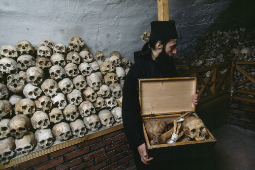 Monks pile the bones of brothers in a charnel house.